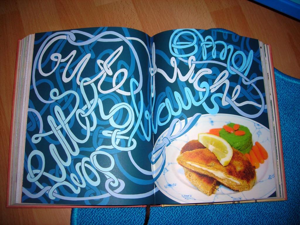 Aufgeklapptes Kochbuch mit aufwendiger Illustration, die mit dem Gericht verschmilzt