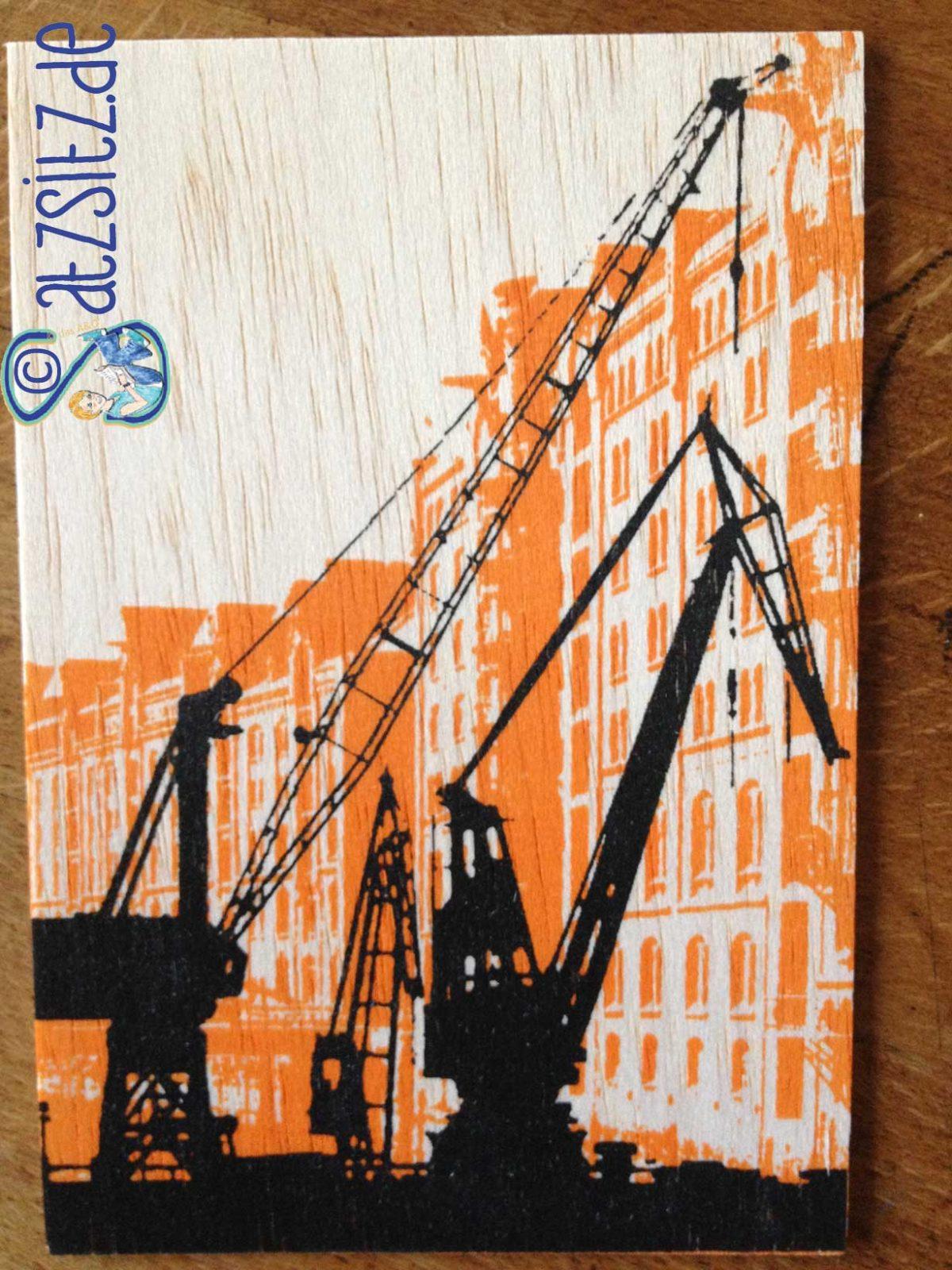 Holzkarte aus Hamburg, die in schwarz-orangen Siebdruck die Speicherstadt mit Kränen zeigt