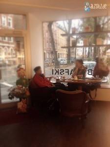 Eingangsbereich des Bukfaski in Mainz mit Kaffeetisch und zwei Gästen.
