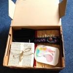 Geöffnetes Päckchen: Blog-Poesiealbum, weißes Kistchen, Fahrradschlauch und Eichhörnchenkarte inside