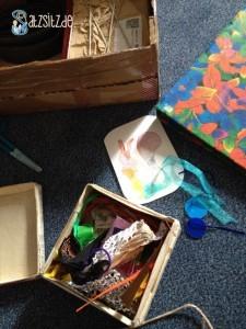 Eine gebastelte Kiste mit bunten Stoff- und Papierkleinigkeiten vor dem geöffneten Päckchen