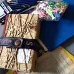 das Upcycling Blog-Buch, daneben die erste Seite einer vergilbten Buchseite und Bastelkram auf dem blauen Teppich