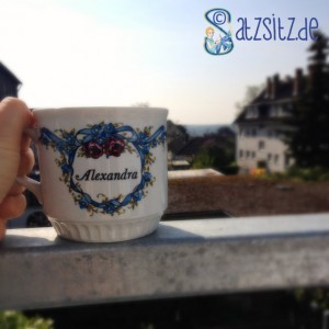 Tasse mit kitschigen Namensaufdruck vor einer Balkonaussicht