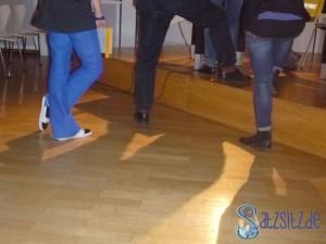 Die letzten drei Menschen stehen vor der Lesebühne an. Man sieht nur ihre Beine. das A&O trägt eine knallblaue Hose, ein Fuß wartend überkreuzt.