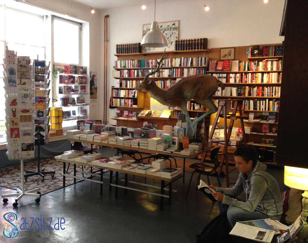 Eingangsbereich der Buchhandlung Buchkönigin: Postkarten, Büchertisch mit Hirschdeko, Buchregale und gemütliche Sessel