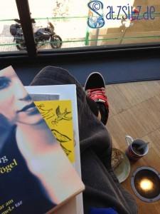 das A&O fotogrsfiert Bücher auf dem Schoß, Kaffee und Kuchen auf dem Boden, sich auf dem Balkon der Altmoeller'schen Buchhandlung