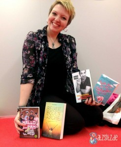Anka von Ankas Geblubber sitzt lächelnd auf dem roten Teppich und präsentiert ihre Bücher