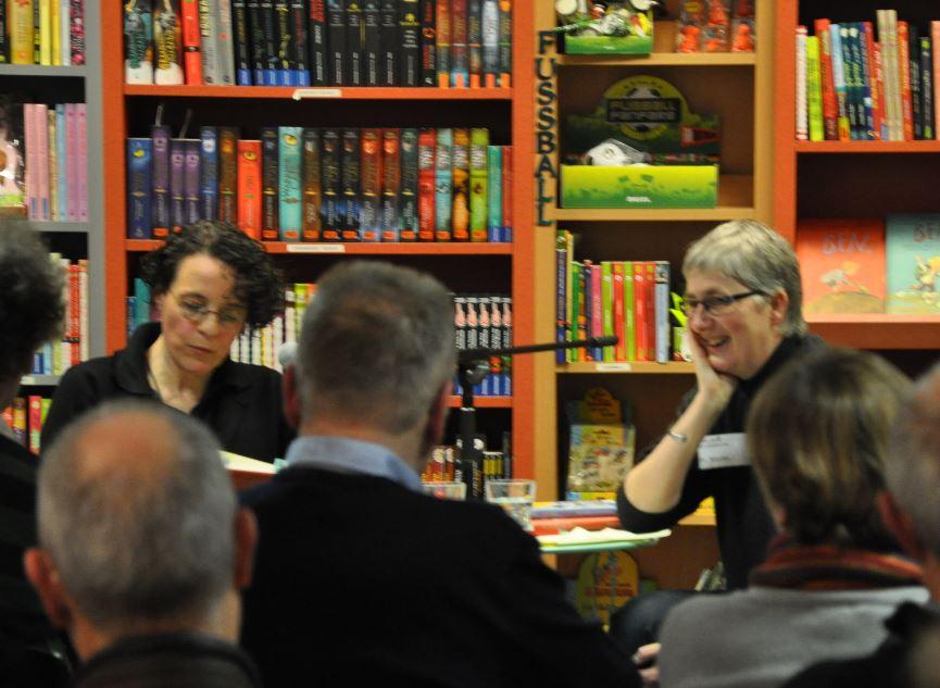 Susanne Martin und Adrienne Braun lachend und lesend in der Schiller Buchhandlung