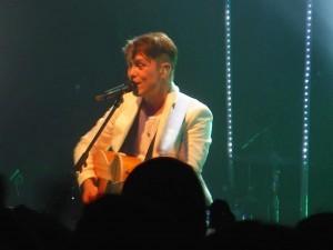 Mark Owen mit Gitarre, schickem Outfit und kleiner Elvistolle