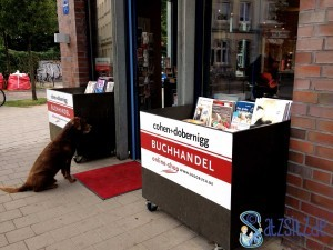 Eingangsberich der Hamburger Buchhandlung cohen+dobernigg. Vor der Tür sitzt ein sehnsüchtig blickender Hund.