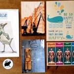 5 bunte Kunst- und Postkarten aus Hamburg schön angeordnet auf einem Holztisch.
