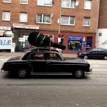 Vor einer Hamburger Ampel hält ein schickes, altes Auto mit riiiesigem Instrument auf dem Dach!