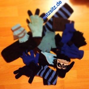 17 einzelne blaue und schwarze Handschuhe, die locker auf dem Boden liegen.