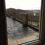 Durchs Fenster den Balkon und Aussicht auf Marbach fotografiert: dunkle Wolken und Pfützen.