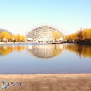 Messehalle in Leipzig von außen, spiegelt sich im davorliegenden See