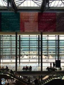 Relativ leere Rolltreppen und hohe Glasfront mit buntem Abschluss