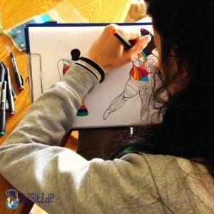 Junge Frau malt ein buntes Bild zweier Frauensilhoetten aus (über ihre Schulter fotografiert)