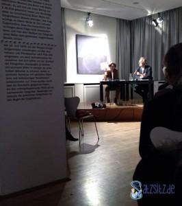 Lesesaal im Stuttgarter Literaturhaus mit Judith Schalanksy auf der Bühne und eine beschriftete Ausstellungswand links im Bild