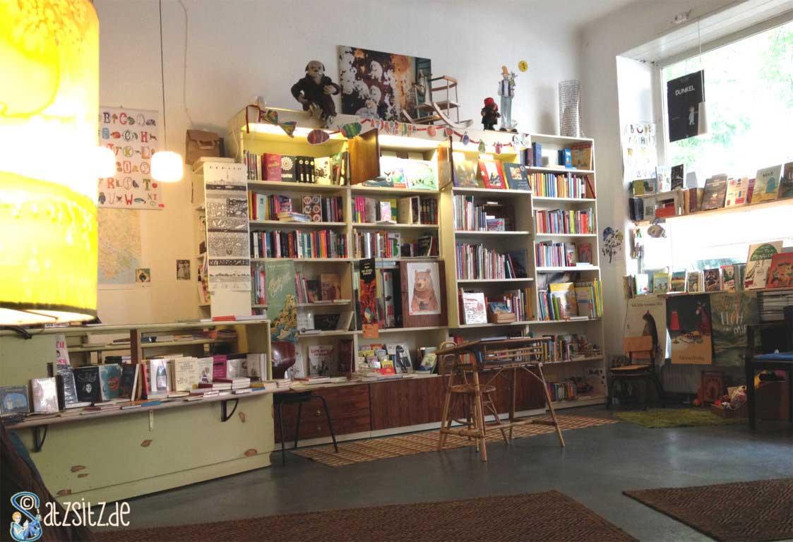 Großes Regal mit Kinderbücher, Plakate und Deko in der Buckönigin. Selbst der Kassenbereich trägt zur gemütlichen Atmosphäre bei.
