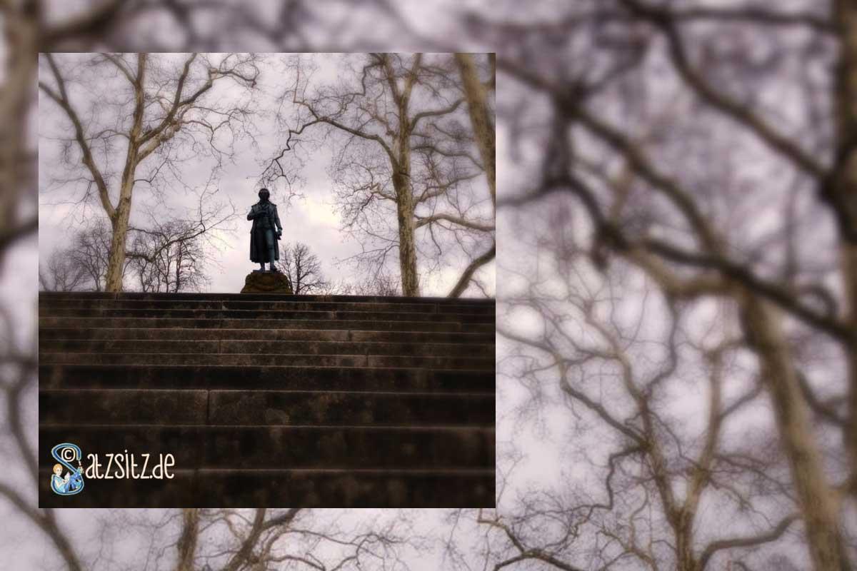 Schiller Statue auf der Schillerhöhe in Marbach vor einer imposanten Baumast-Kulisse