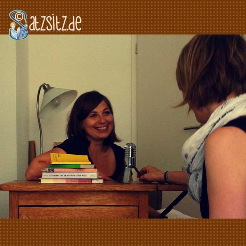 Claudia Feldtenzer und das A&O mit einem Mikrofon und einem Bücherstapel. Aufnahme zum Literatur Podcast.