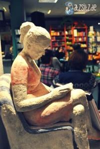 Weiße Statue einer lesenden Frau (vorne), im Hintergrund die Lesung in der Buchhandlung