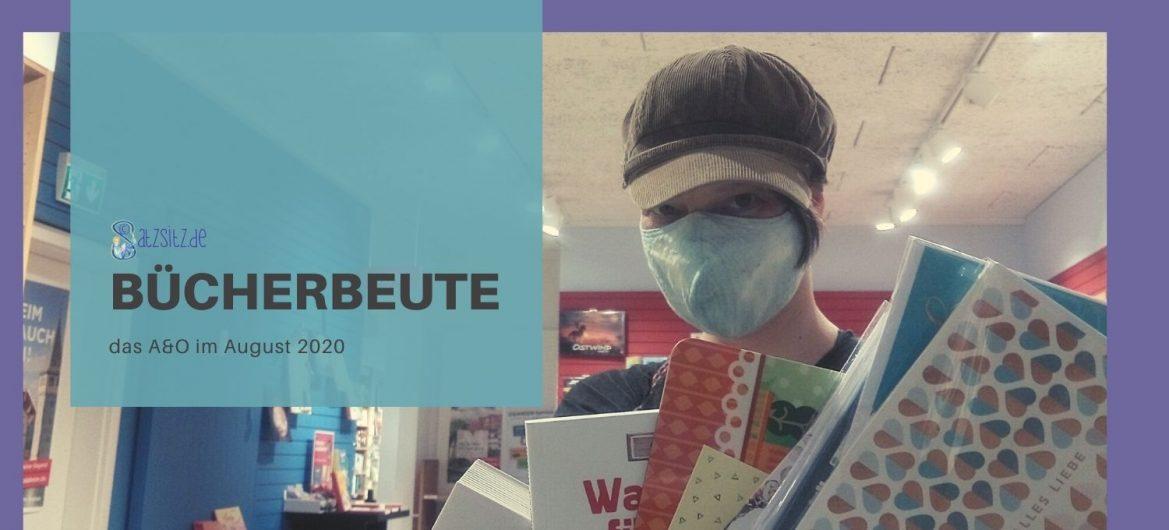 das A&O steht mit Mund-Nasen-Schutz im Buchladen und hält Bücher hoch