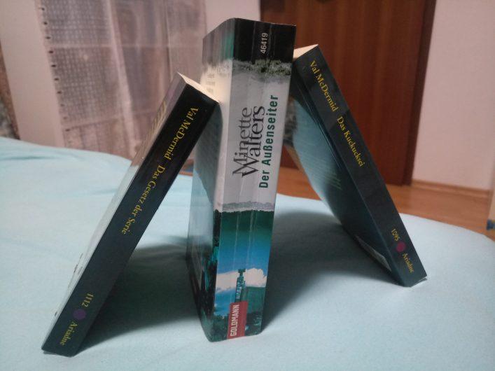 Drei Krimis lehnen stehend aneinander und strecken ihre Buchrücken ins Bild