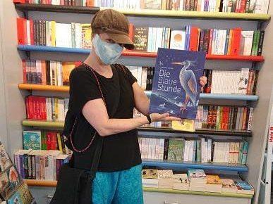 das A&O mit Mundschatz im Buchladen. Hält ein blaues Buch hoch